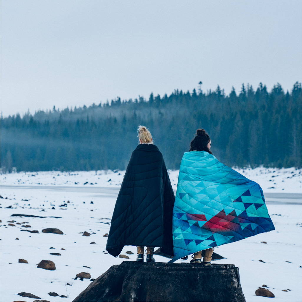 Two women standing on a frozen lake with Rumpl blankets