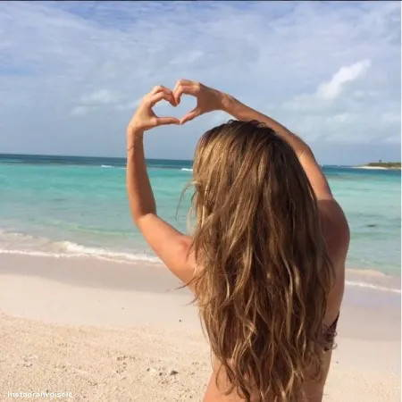 Girl on the beach with long wavy hair making a love heart with her hands