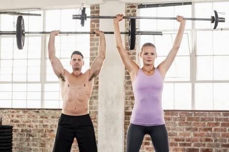 Frau und Mann beim Schulterdrücken mit der Langhantel