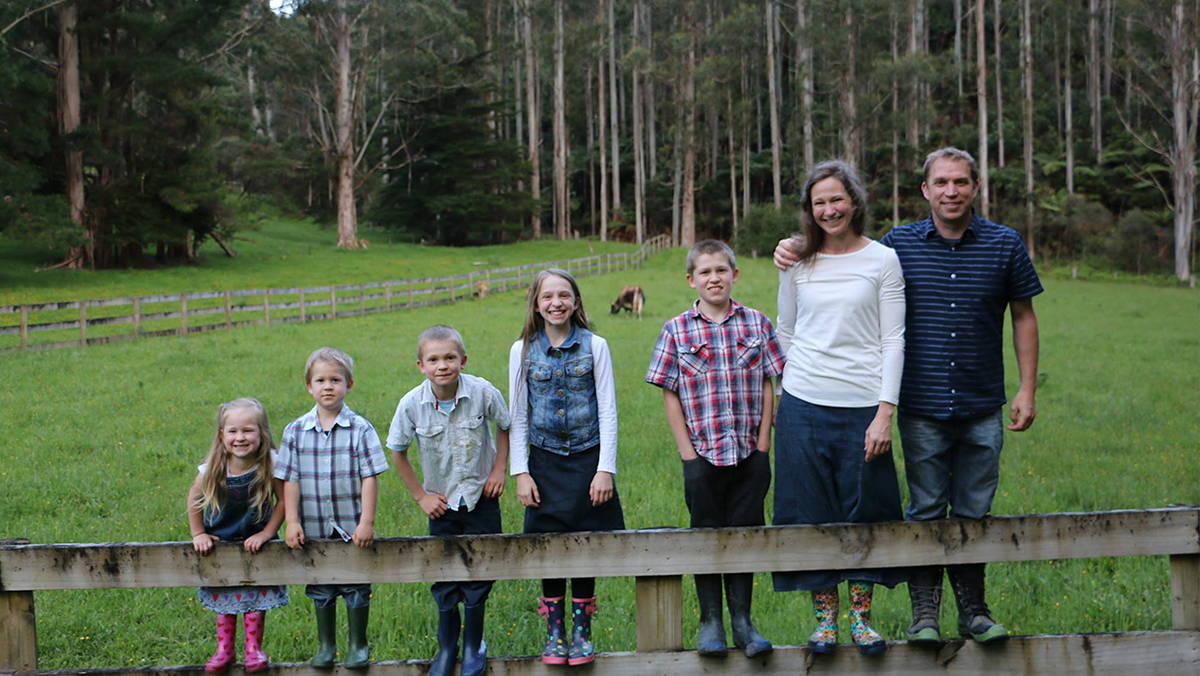 family of seven standing on a farm fence
