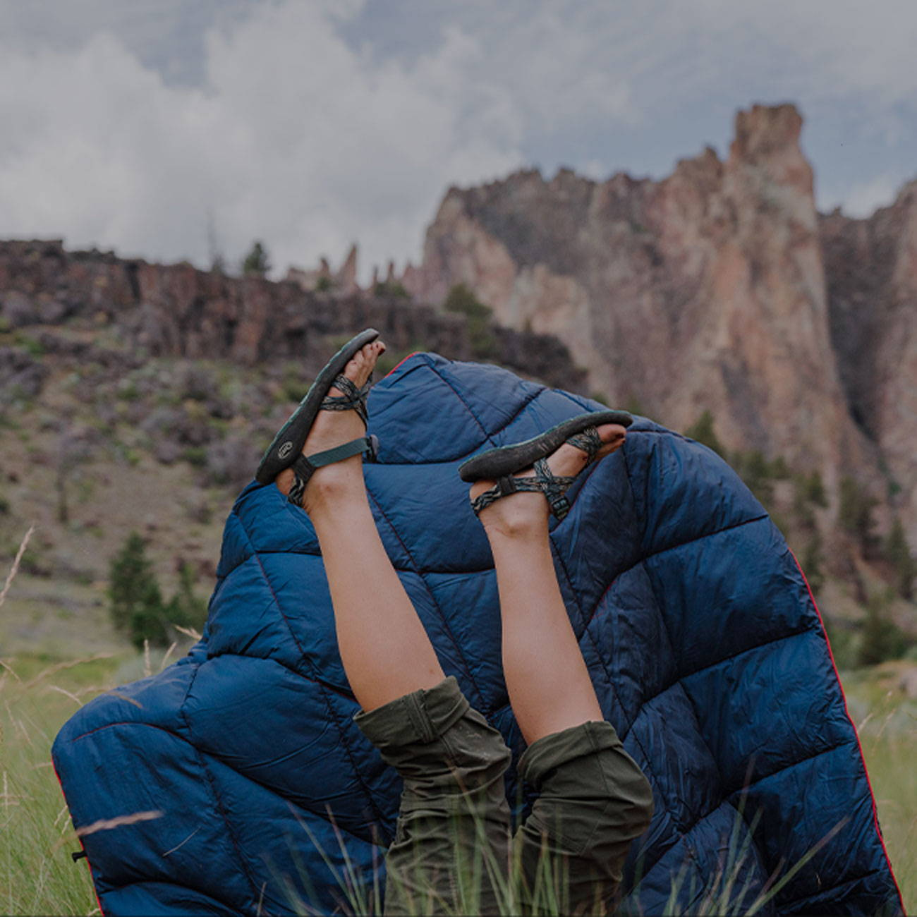 Person laying outdoors in a canyon in sandals and a warm Rumpl blanket