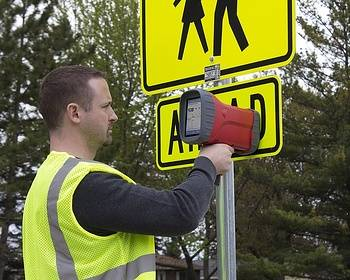 Traffic manager testing reflectivity of road sign