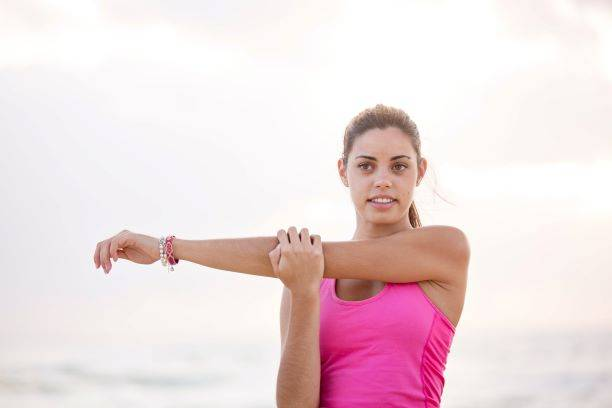 Woman In Pink Top Stretching Her Arm