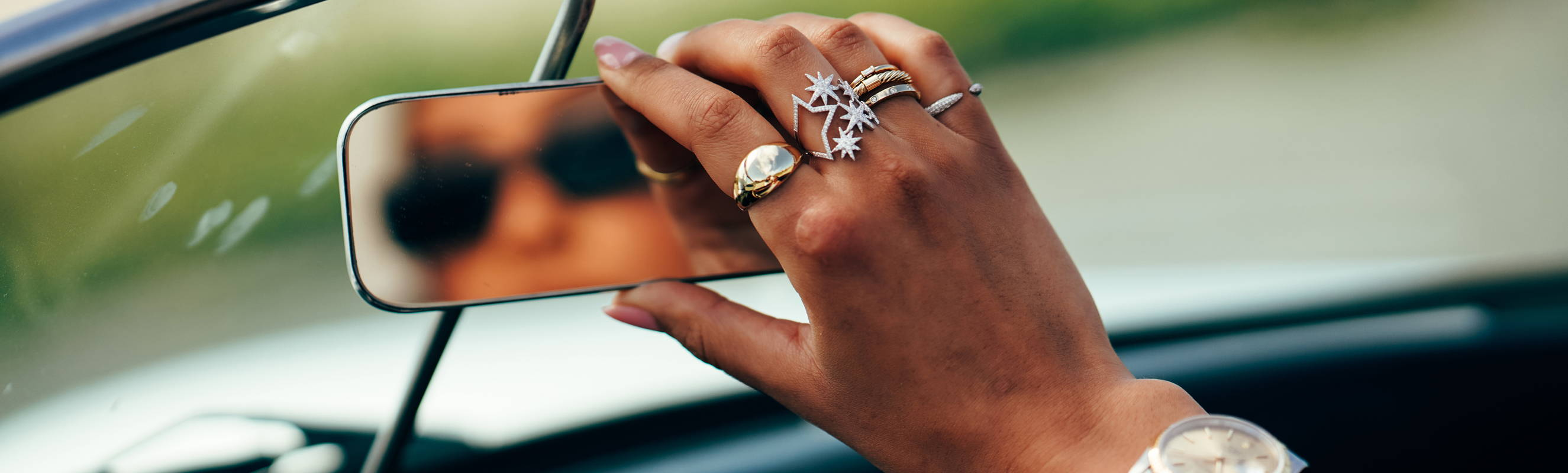 Model adjusting car mirror wearing Ring Concierge fine jewelry