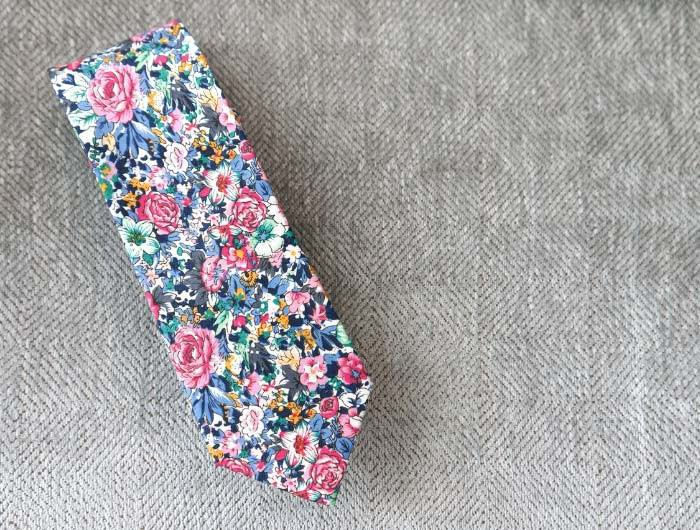 Dusty blue and pink floral tie on a gray background