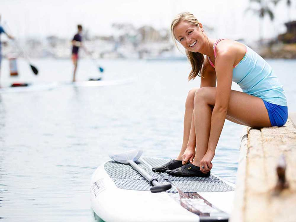 Girl sat on the bank putting shoes on while feet are on the paddle board