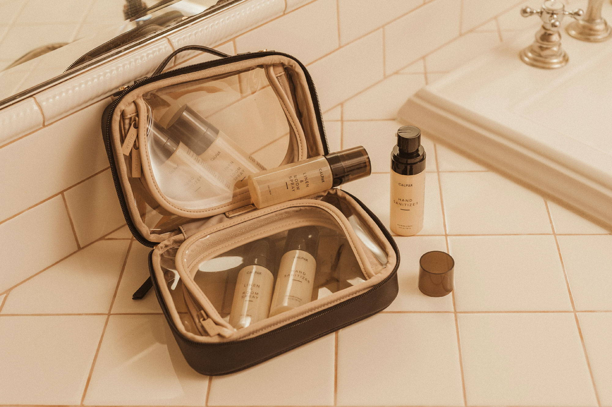 CALPAK Mini Clear Cosmetics Case in Eclipse, Everyday Hand Sanitizer, and Freshen Up Linen & Room Spray.