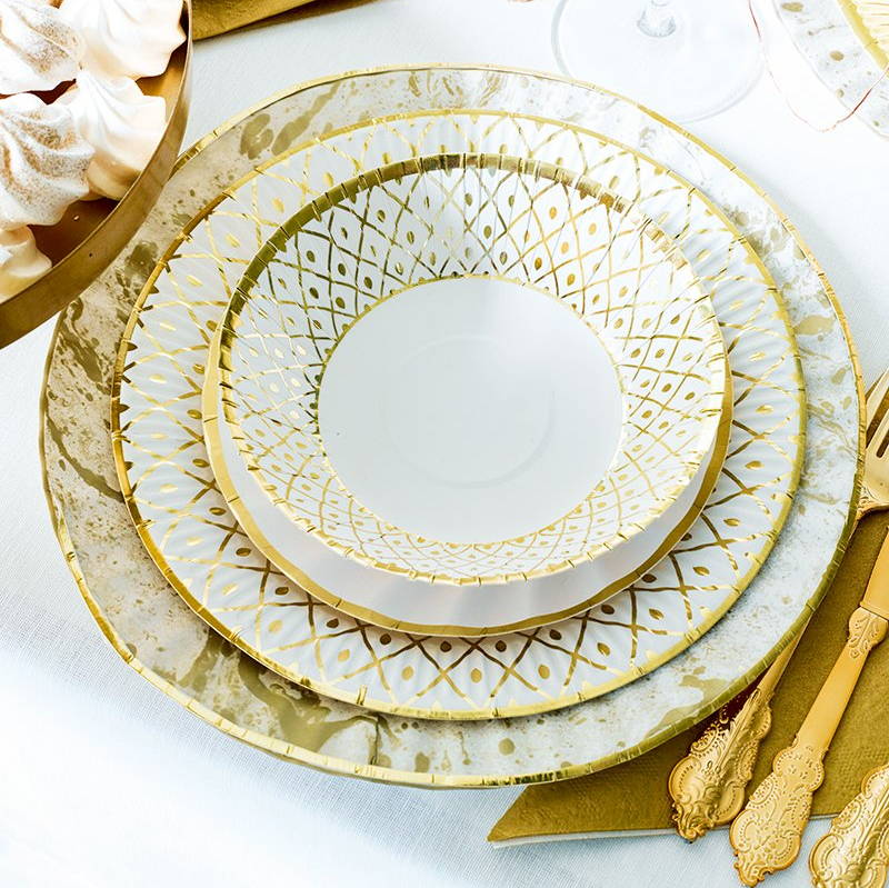 A photo of a wedding place setting with a stack of gold paper plates and gold plastic cutlery for a wedding