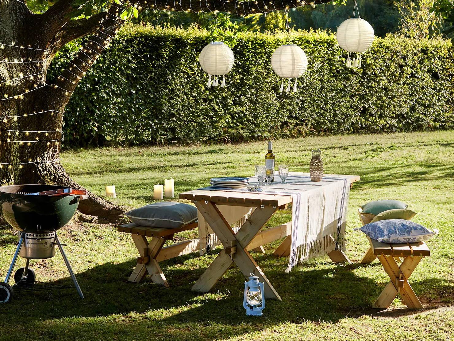 Table de pique-nique avec lampions suspendus, lanterne et guirlande lumineuse.