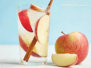 Glass of water with apple slices and cinnamon sticks