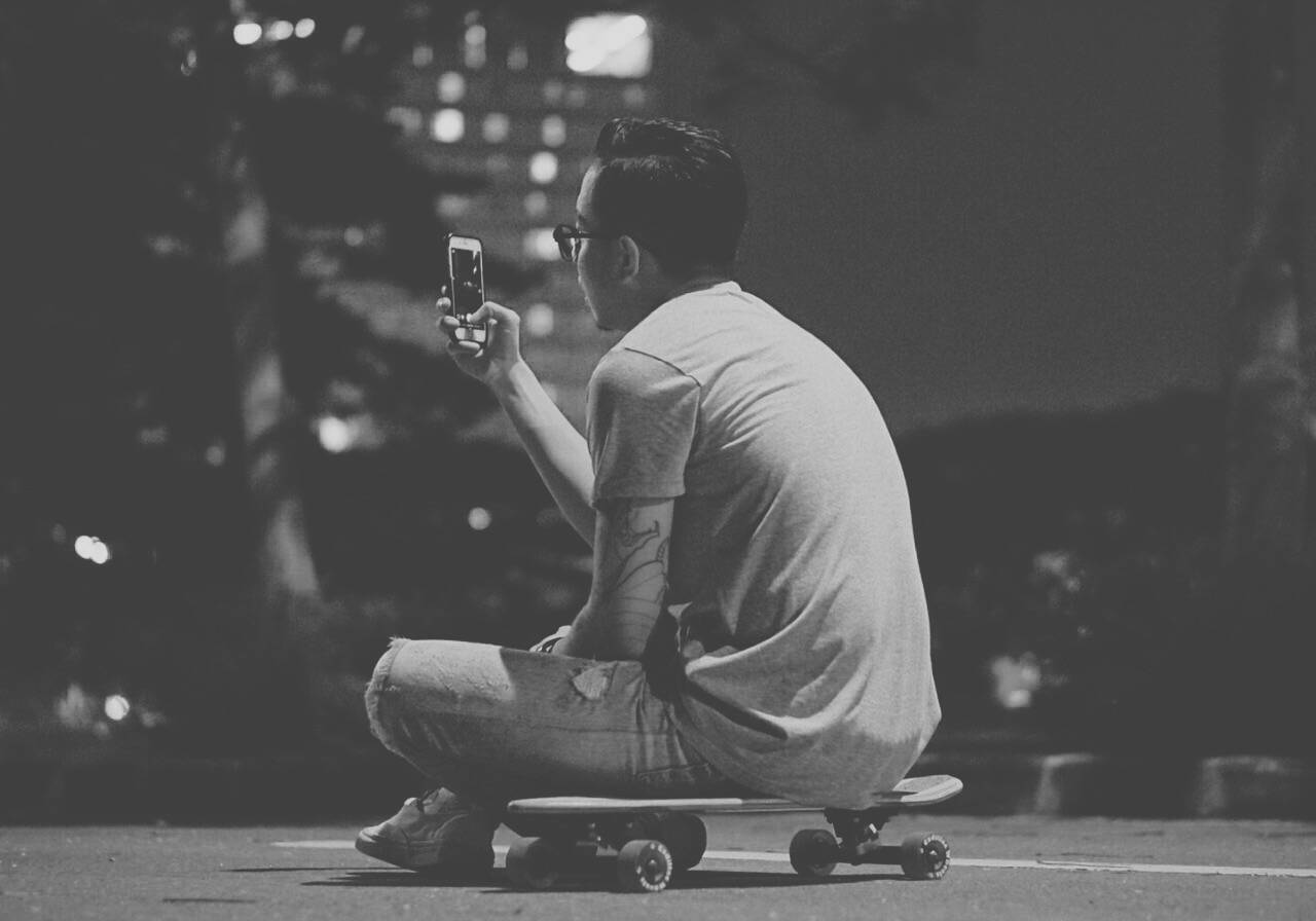 A guy looking at his phone awhile sitting on his skateboard