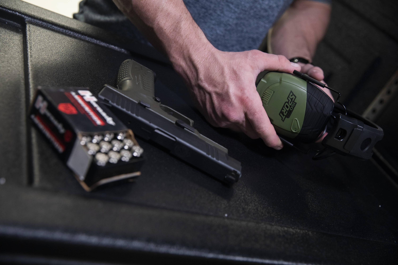 ISOtunes Sport DEFY pictured next to a 9mm caliber handgun