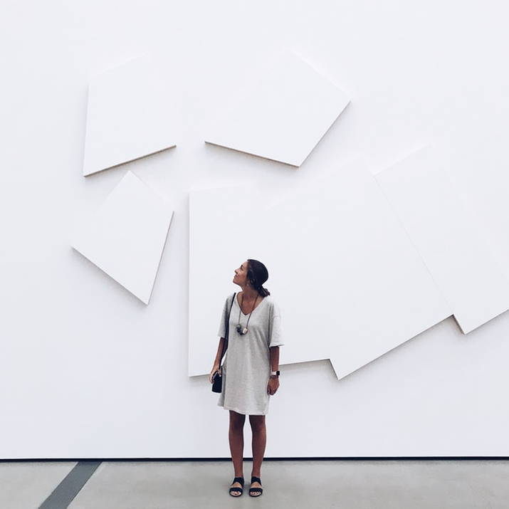 Woman looking at minimalist white art relief