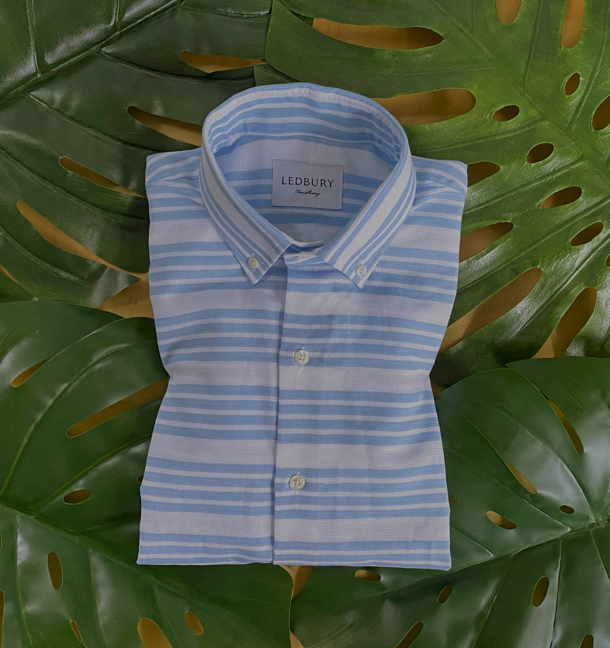 The blue Harlan Stripe Shirt folded on top of tropical leaves.