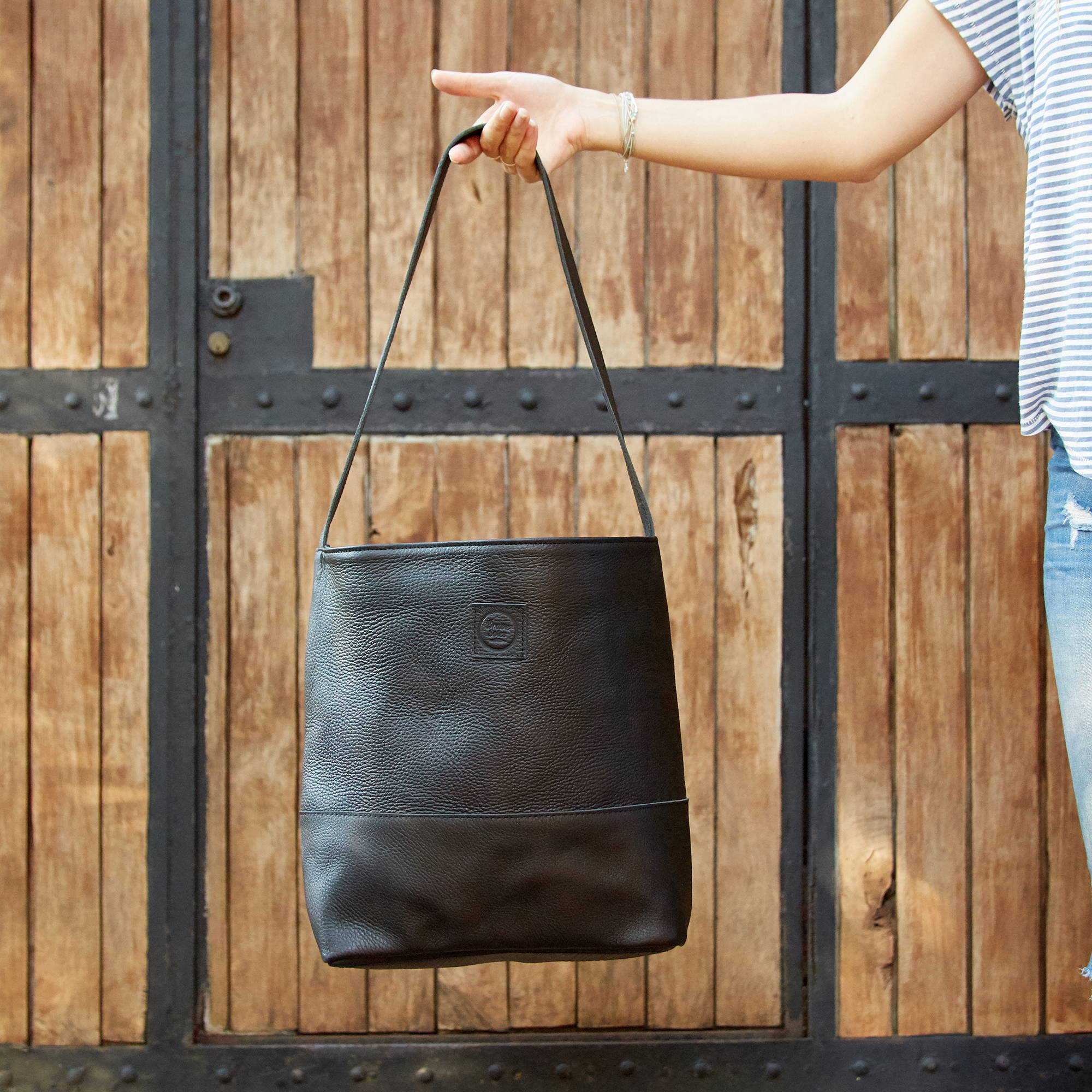 A hand holding an oversized black leather tote bag made of upcycled tires from the Dominican Republic.