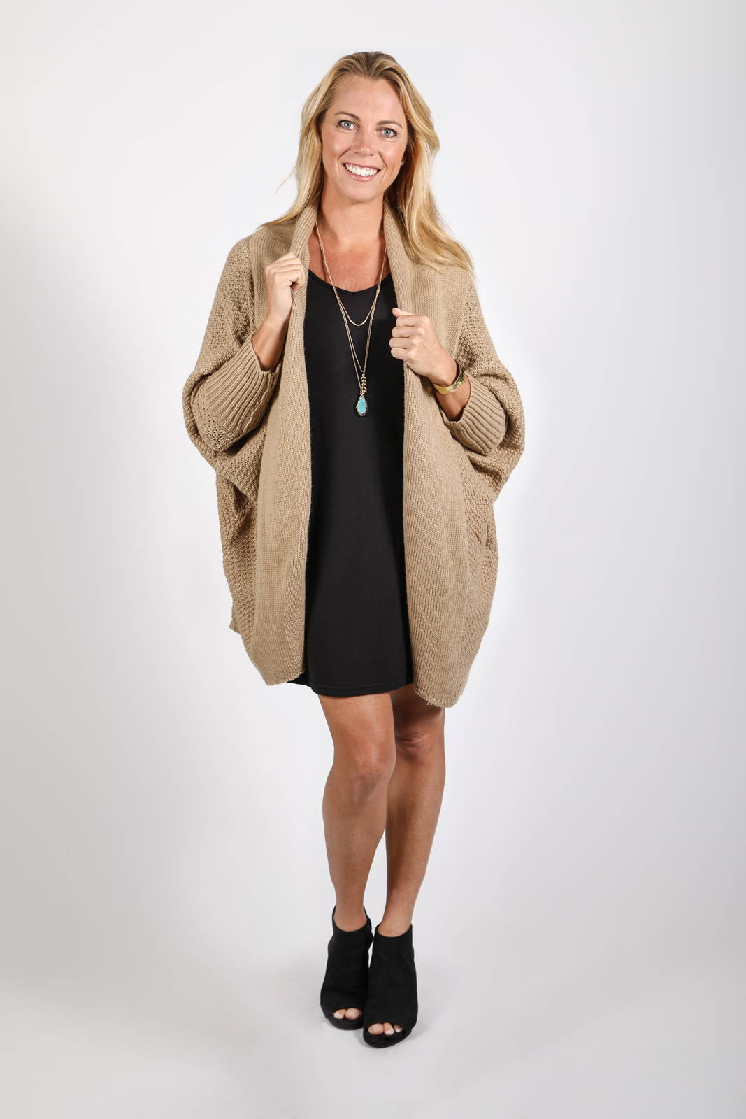 The chunky-knit Zeville Coccoon Cardigan in Camel with the Ina Dress in black, by illuminative