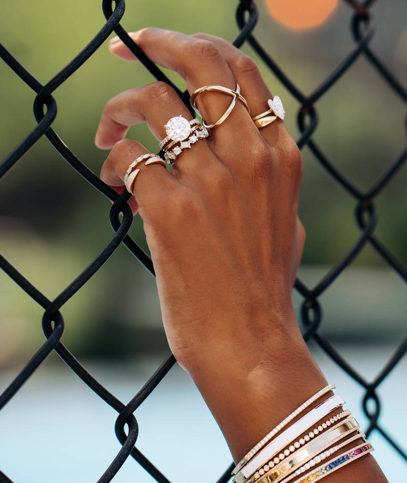 Close up of a hand wearring various Ring Concierge rings and bangles