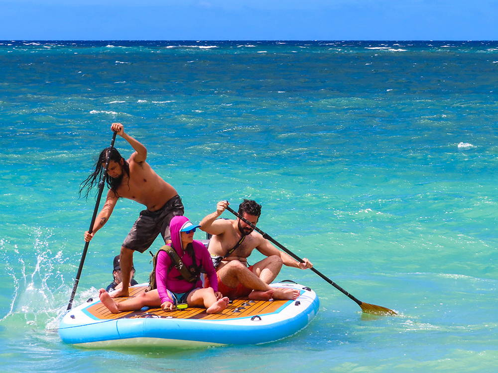 Four people riding the Pau Hana Bimini board on the ocean