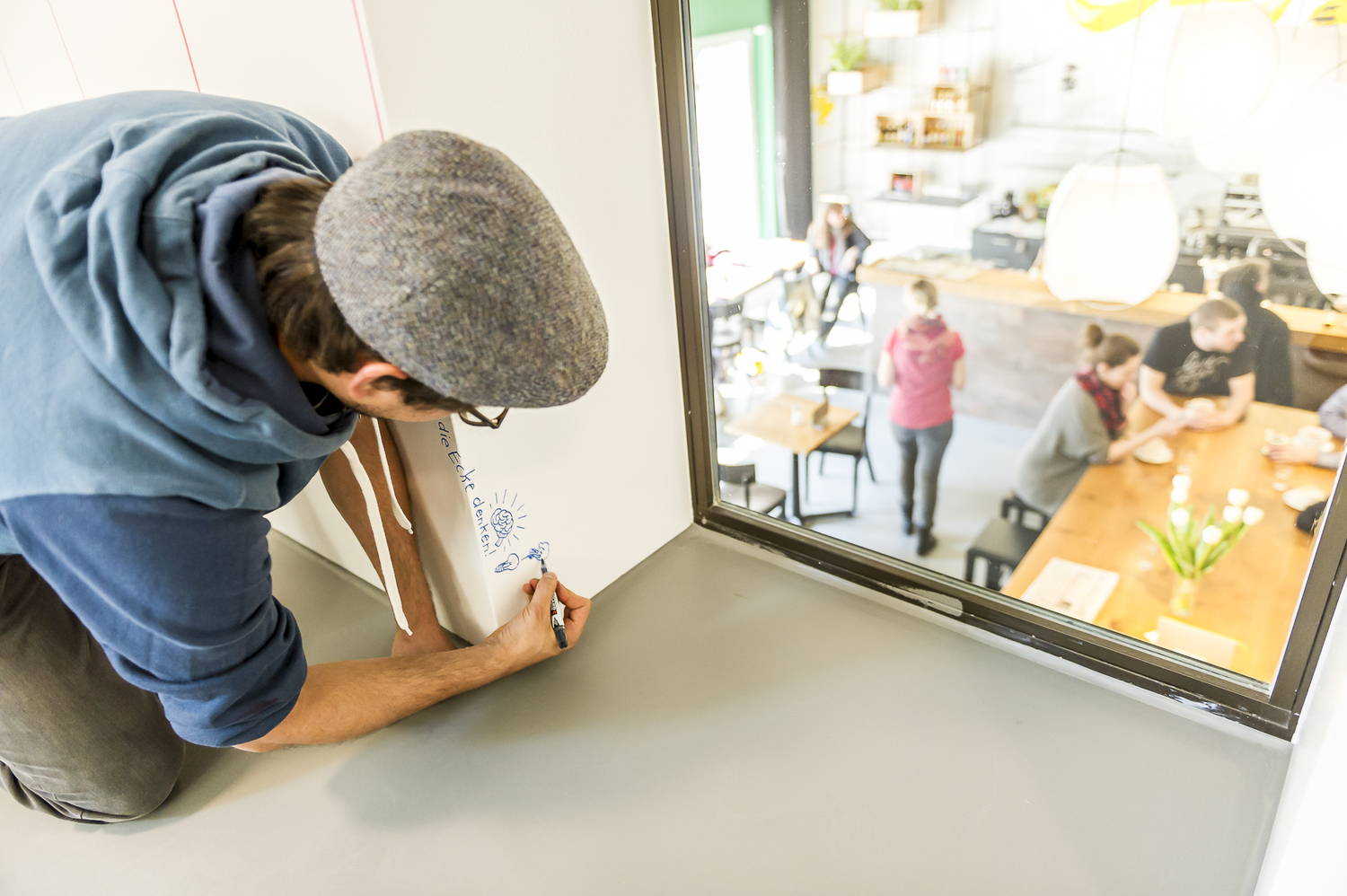 An employee writes on his IdeaPaint dry erase wall at the workplace.
