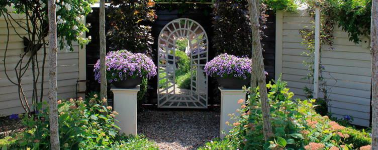 Un miroir suspendu au détour du jardin pour un parfait trompe-l'œil de style anglais.