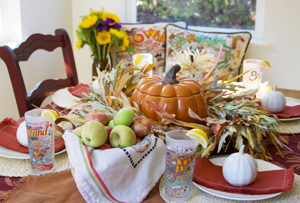 A fall table with pumpkins, apples, and fall table linens along with catstudio Geography glasses, dish towels, and pillows