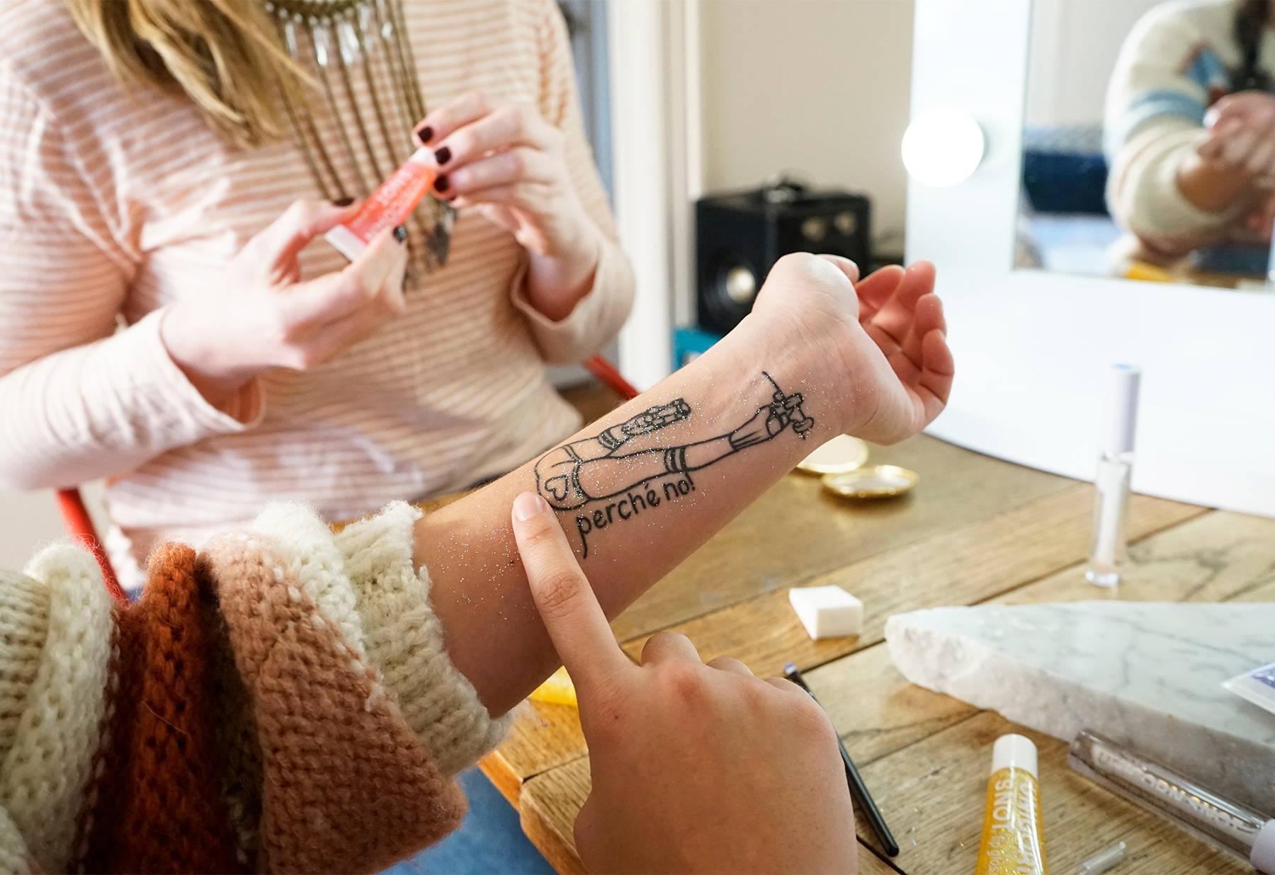 Amanda puts silver Unicorn Snot glitter gel on her tattoo.