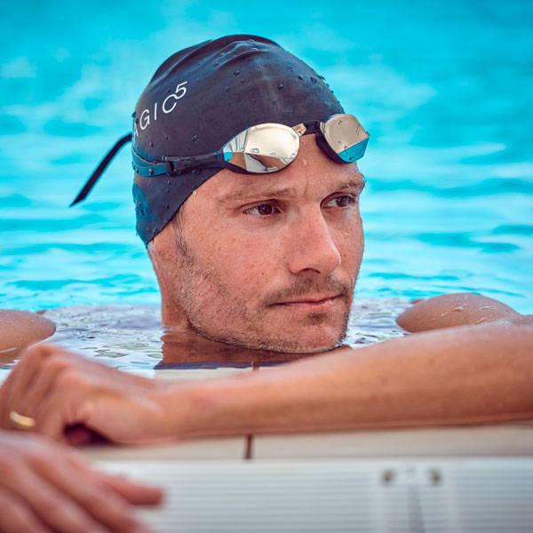 Jan Frodeno sitting on the edge of the pool with goggles on his head.