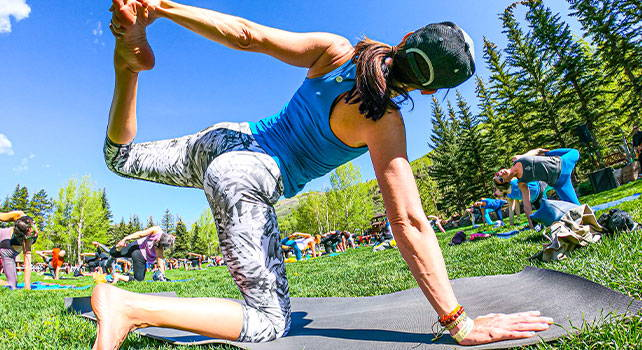 People doing yoga in a grassy field. Photo Credit: Zach Mahone