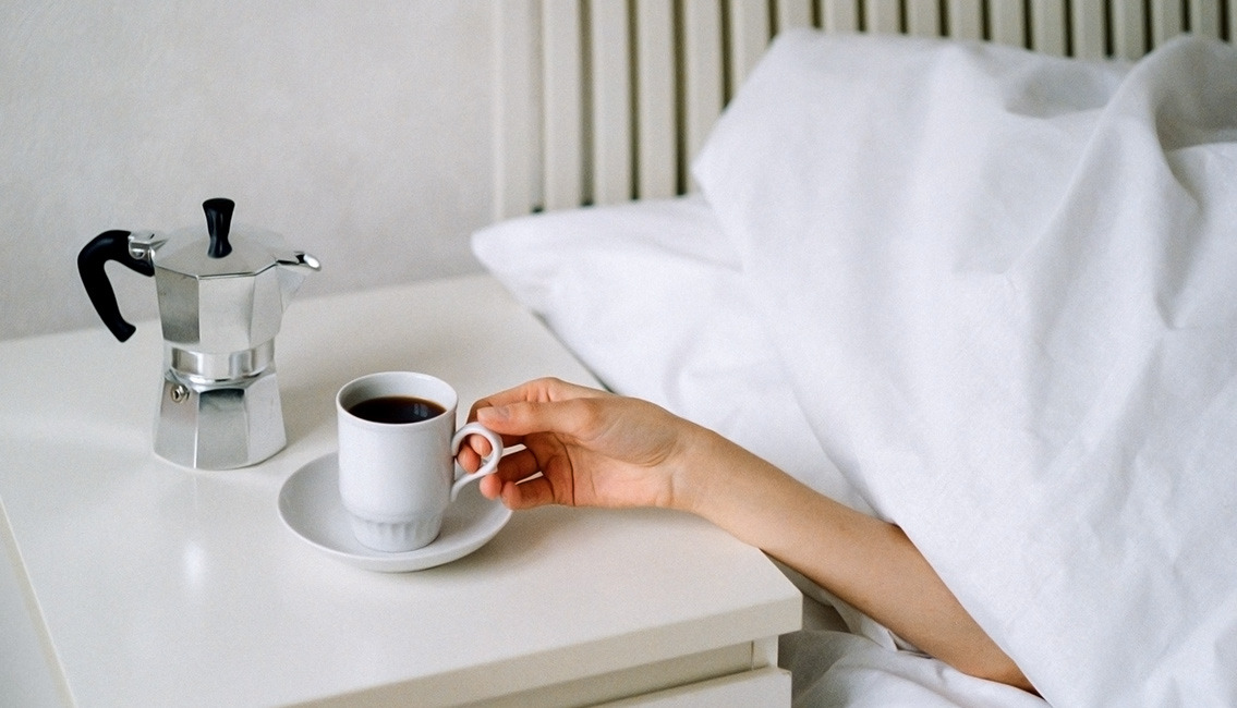 Person in bed, reaching for a cup of coffee on night stand. heroimage