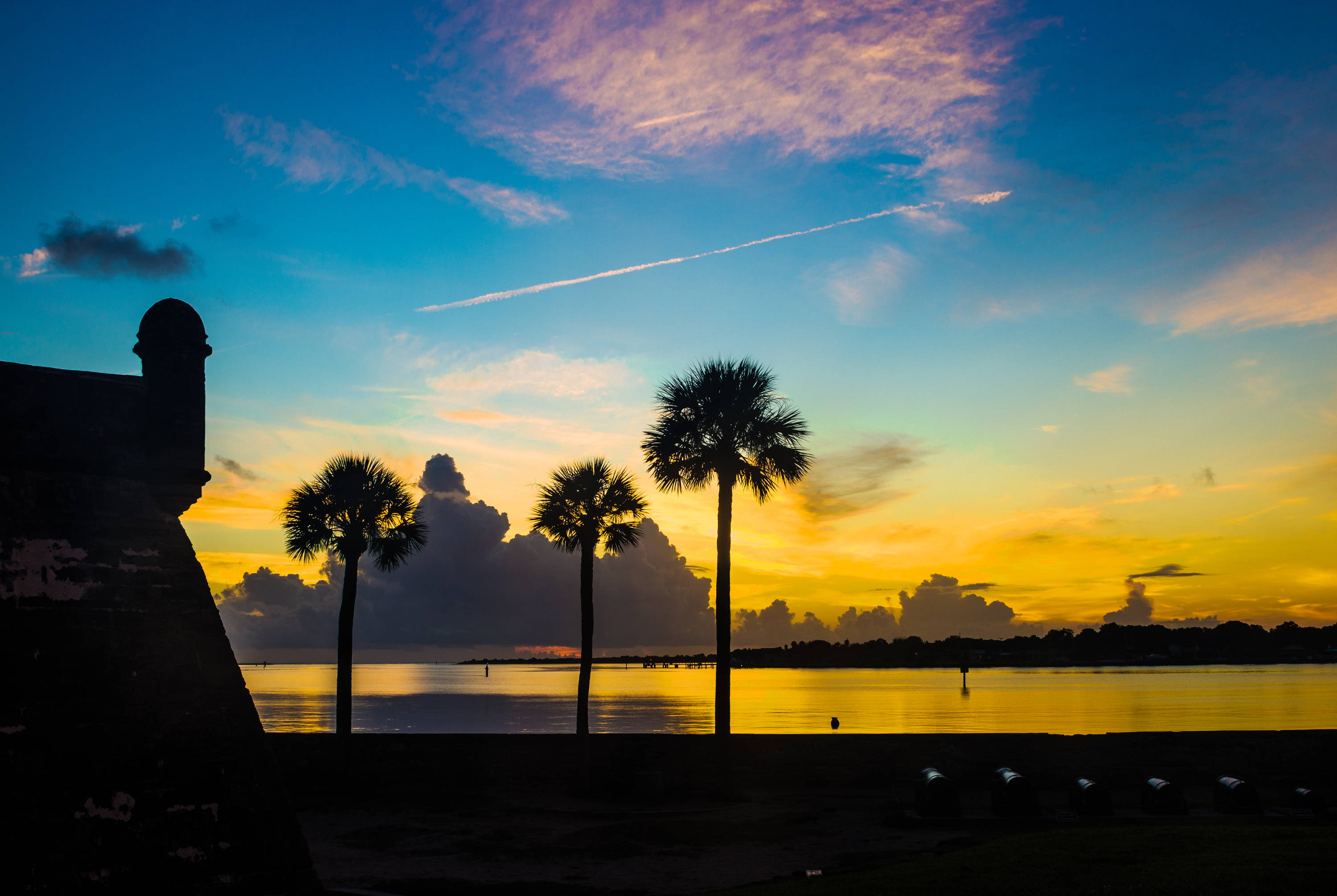 National Parks in Florida. Sun sets over water with yellow and blue hues, clouds in the background, and palm trees in the foreground.