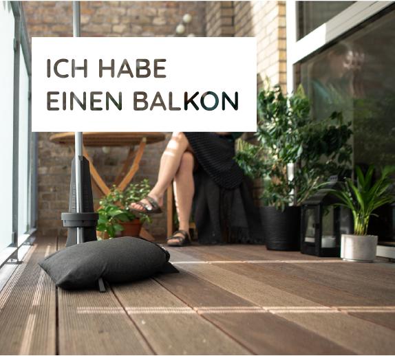 Balkonschirmständer von Baser mit einem dunkelgrauen Sandsack auf einem Balkon