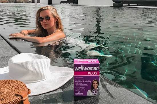 Woman In Siwmming Pool Next To Wellwoman Product
