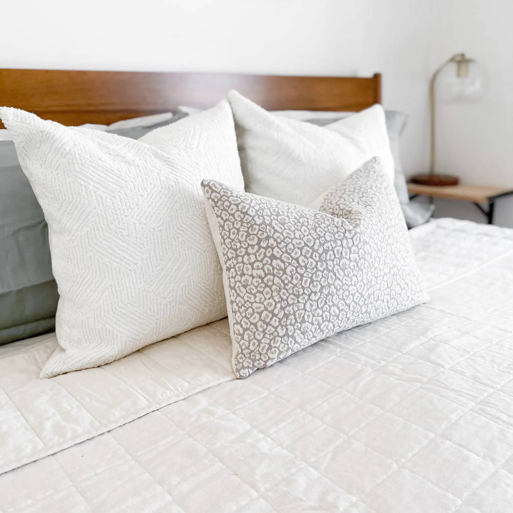 Colin and Finn Darcy white textured pillows with Josephine Lumbar Pillow on king bed with ivory quilt