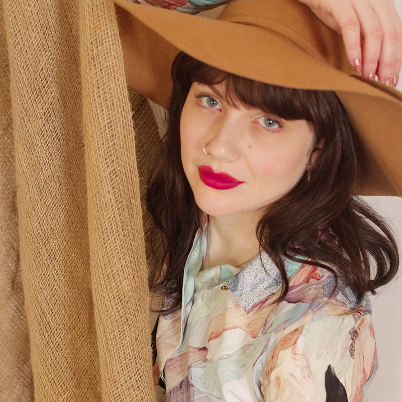 Brunette girl wearing a brown floppy hat and floral printed vintage shirt