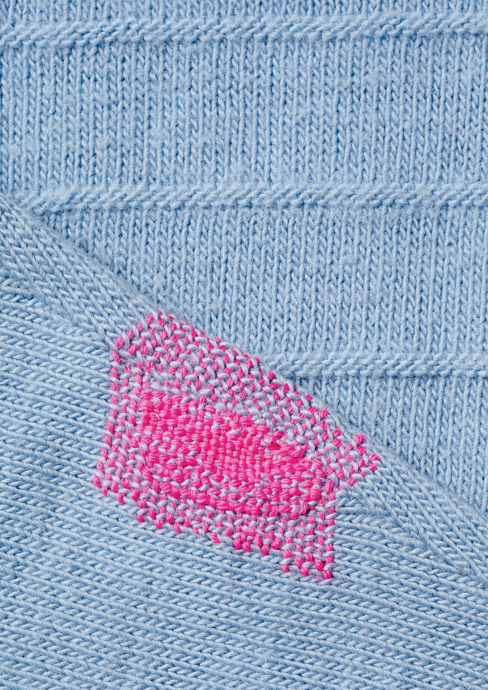 Powder blue sweater from TOAST with mended parts.