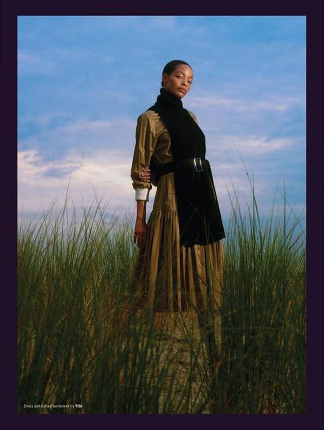 Tidal Magazine editorial image. Model standing in a field wearing a khaki dress and black dickie.