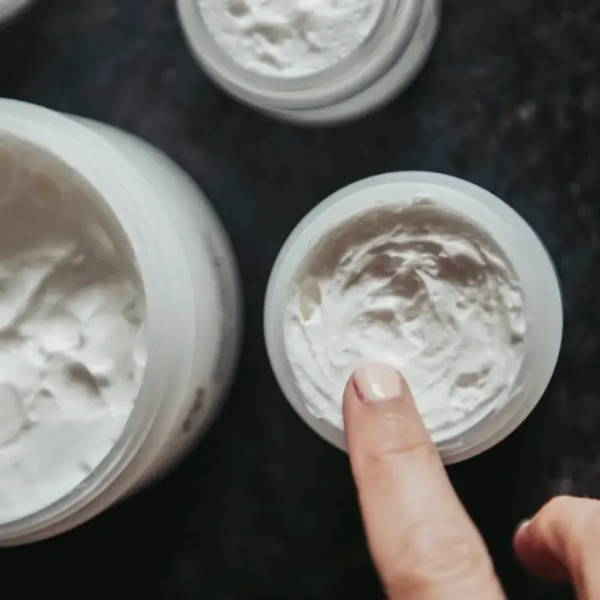 Finger dipping into jar of Truly O2 oxygen moisturizer