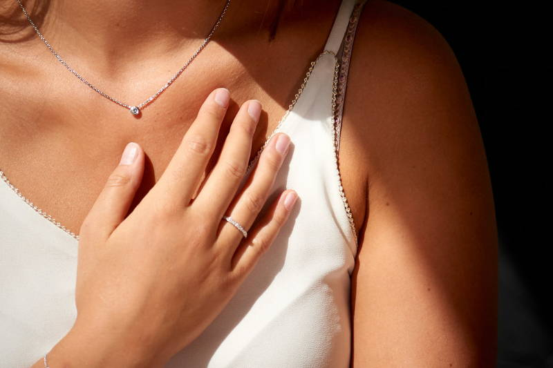 hand with diamond rind and necklace