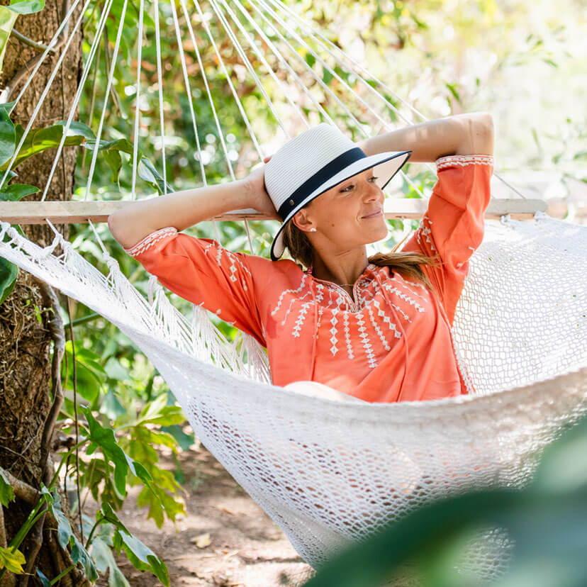 Woman lounging in hammock wearing a hat