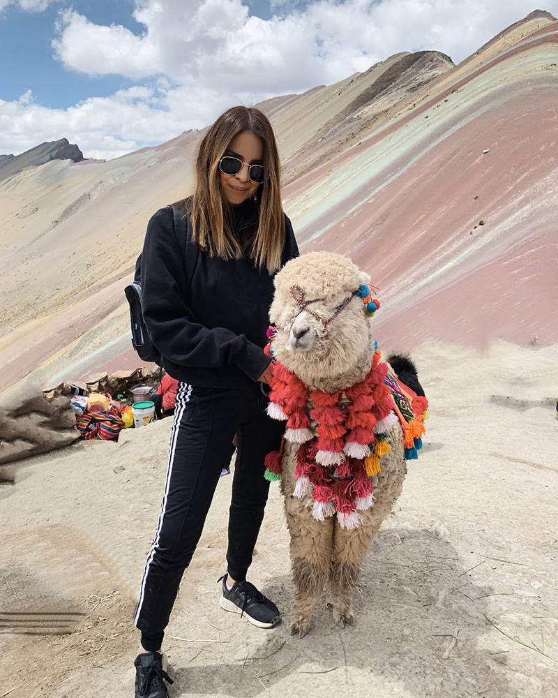 Giselle Romero visiting Alpaca in Machu Picchu.