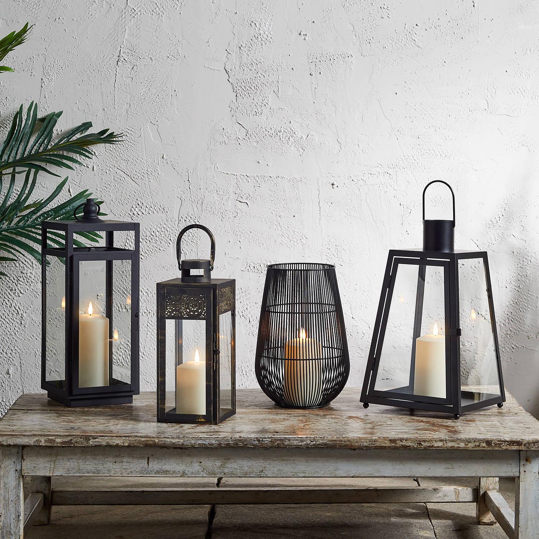 Lanternes d'extérieur posées sur table basse en bois.