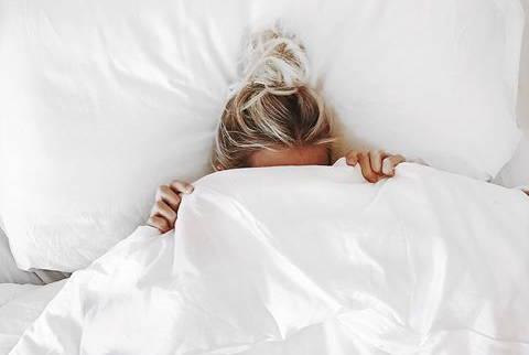 Blond girl hiding under her silky soft Eucalypso organic eucalyptus sheets in white