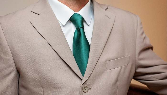 Man wearing tan suit and hunter green tie