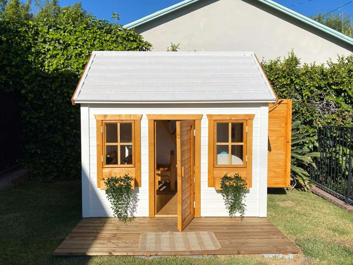 Wooden playhouse with a wooden porch and flower boxes with green plants by WholeWoodPlayhouses