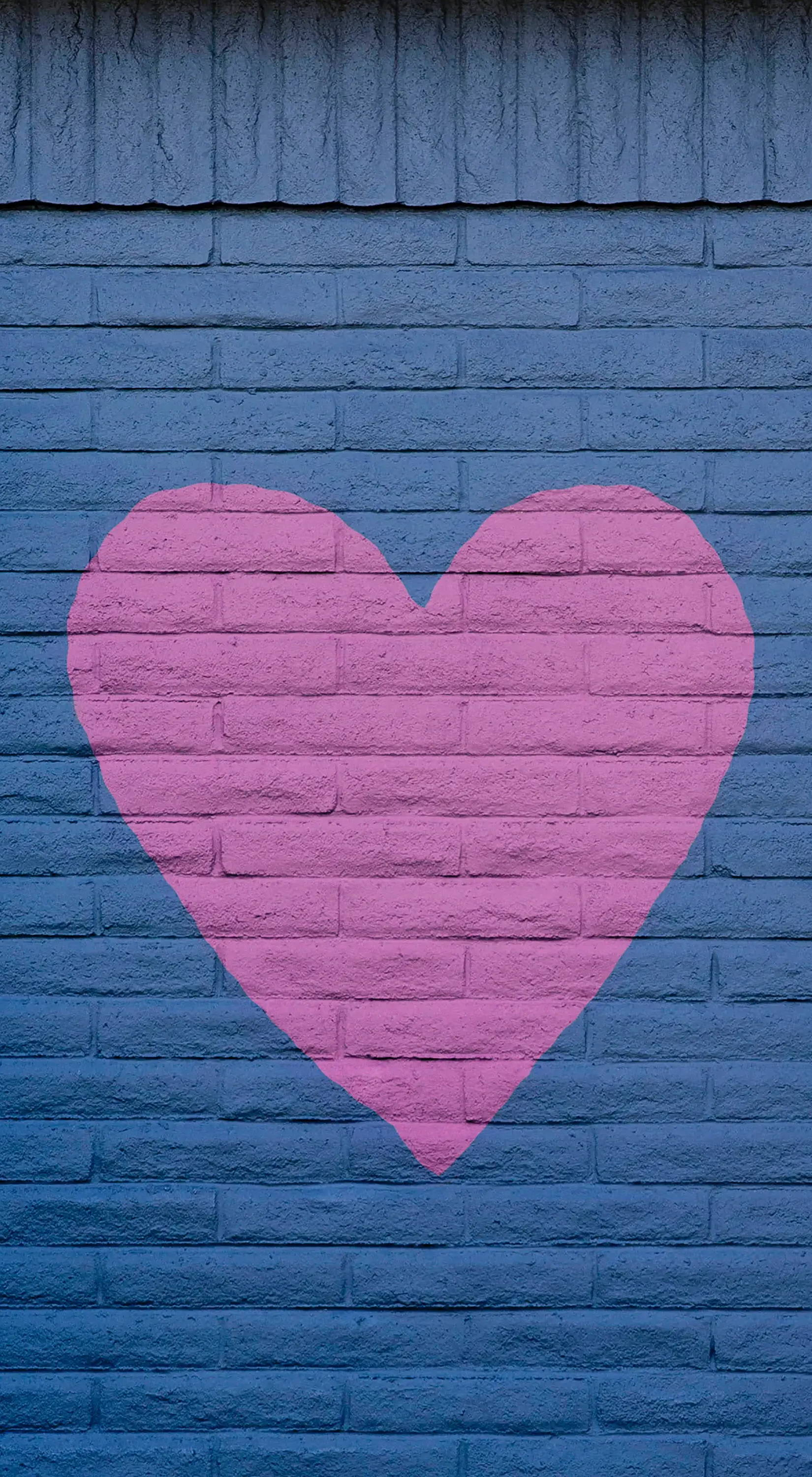 a pink heart painted on a grey wall