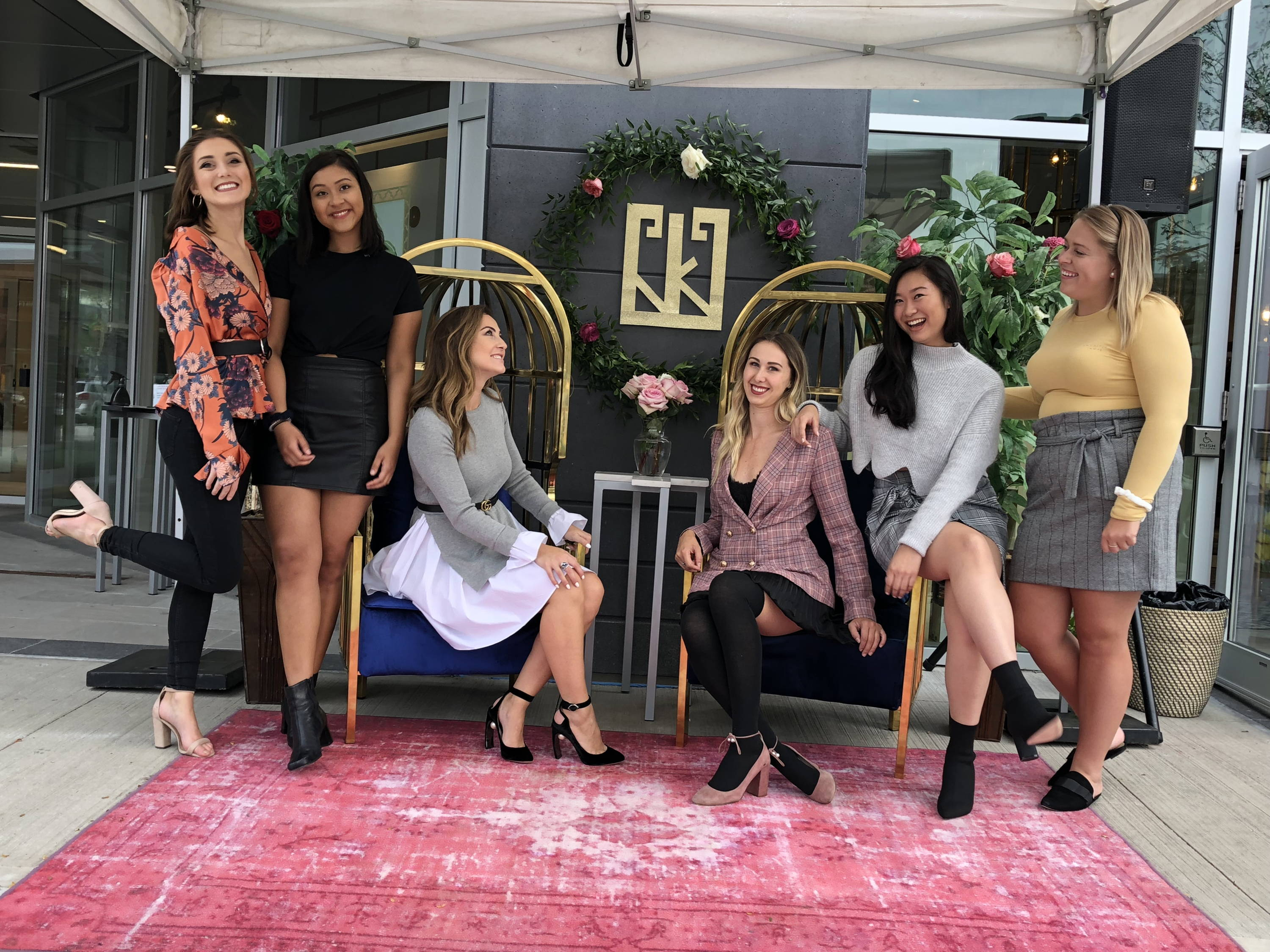 Group of UNI+KONCEPT employees posing for a photo during the store grand opening event in september 2018. located uptown waterloo kitchener. pink rug, two gold chairs.