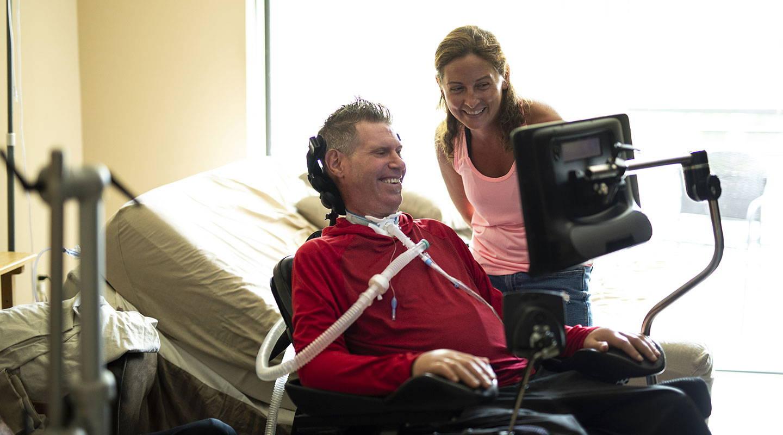 Mann benutzt ein Gerät der I-Serie von Tobii Dynavox mit unterstützender Technologie, das an seinem Rollstuhl befestigt ist