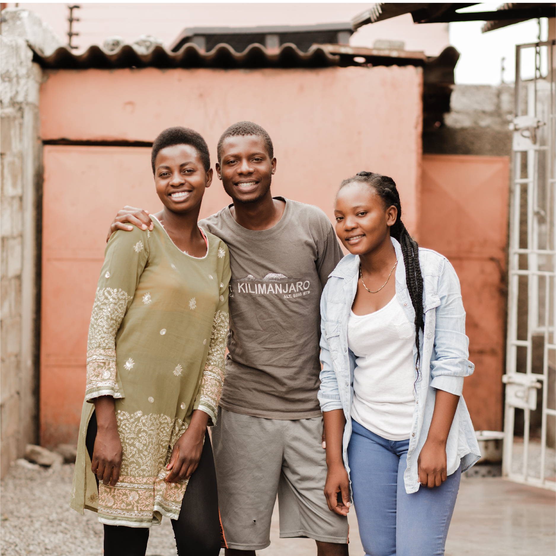 three young adults in Zambia (two girls and a guy) pose with their arms around each other and smile