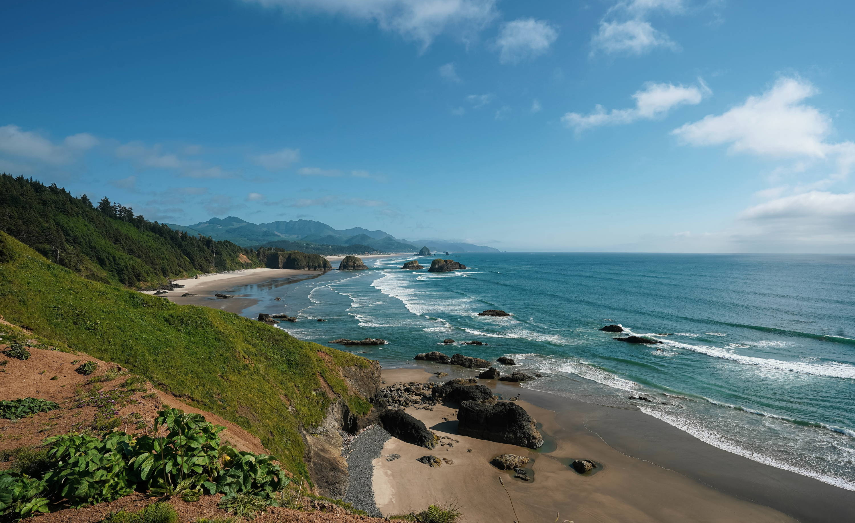 Camping the Oregon Coast. Blue waves crash against rugged rocks and picturesque sand with green hills above.