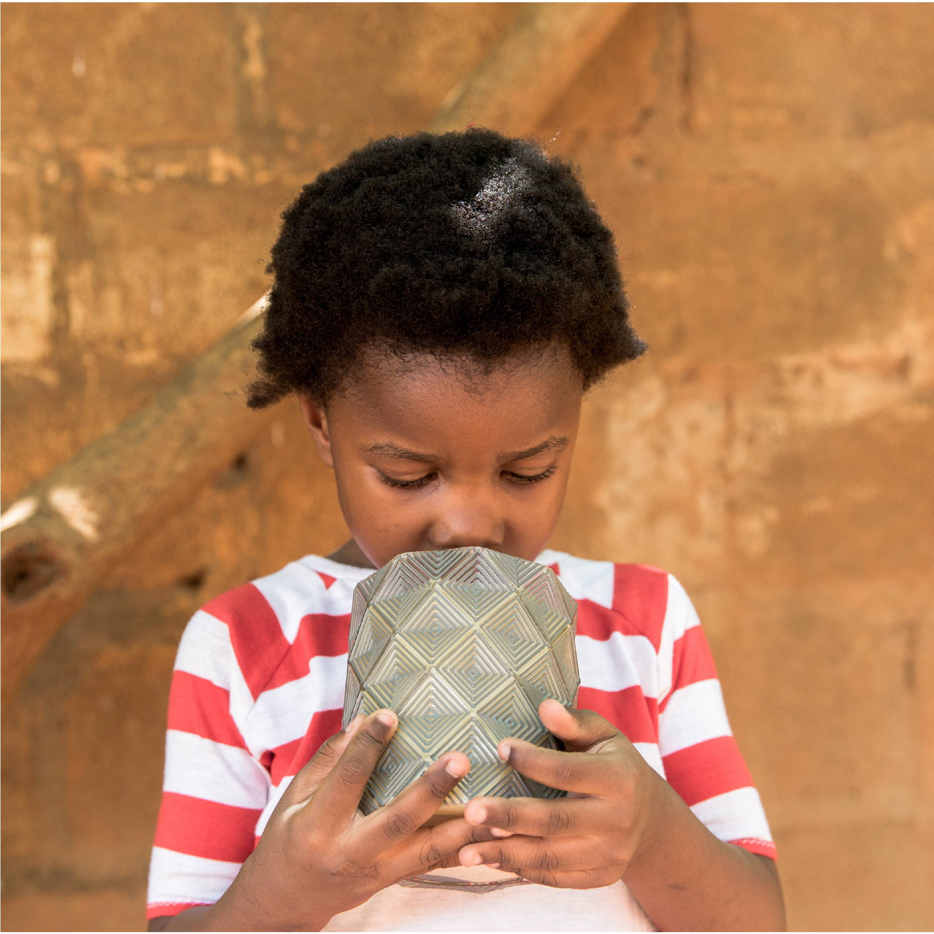 A young Zambian girl wearing a red and white striped shirt smells a Bridgewater Afternoon Retreat Candle.